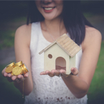 girl holding a house in one hand and coins in the other